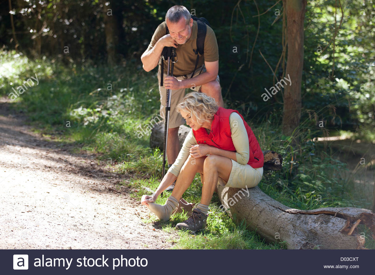 A mature couple resting beside a country path, woman massaging her sore feet - Stock Image