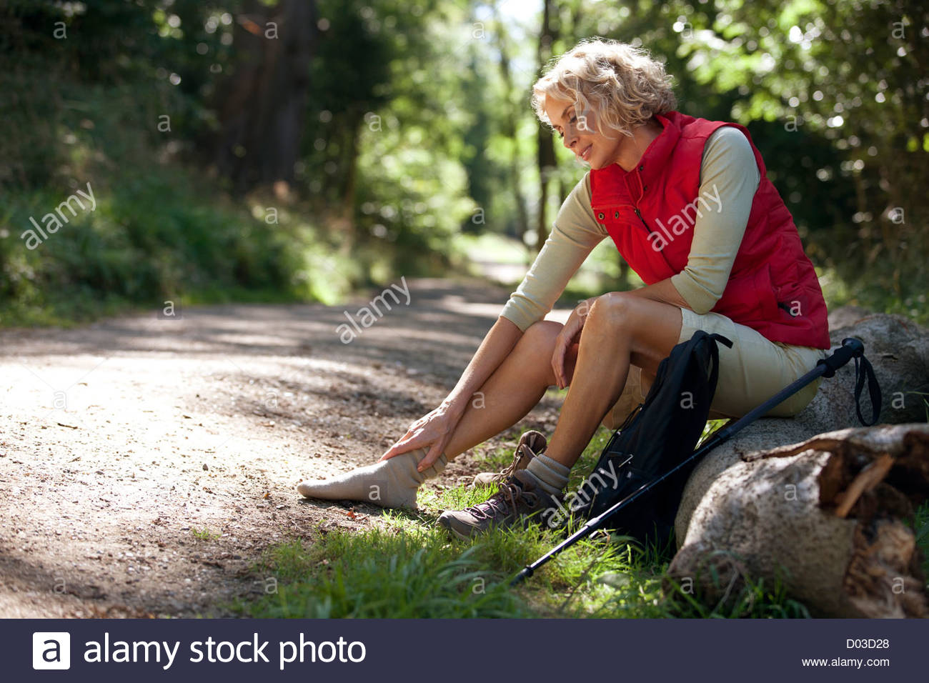 A mature woman resting beside a country path, massaging her sore feet - Stock Image