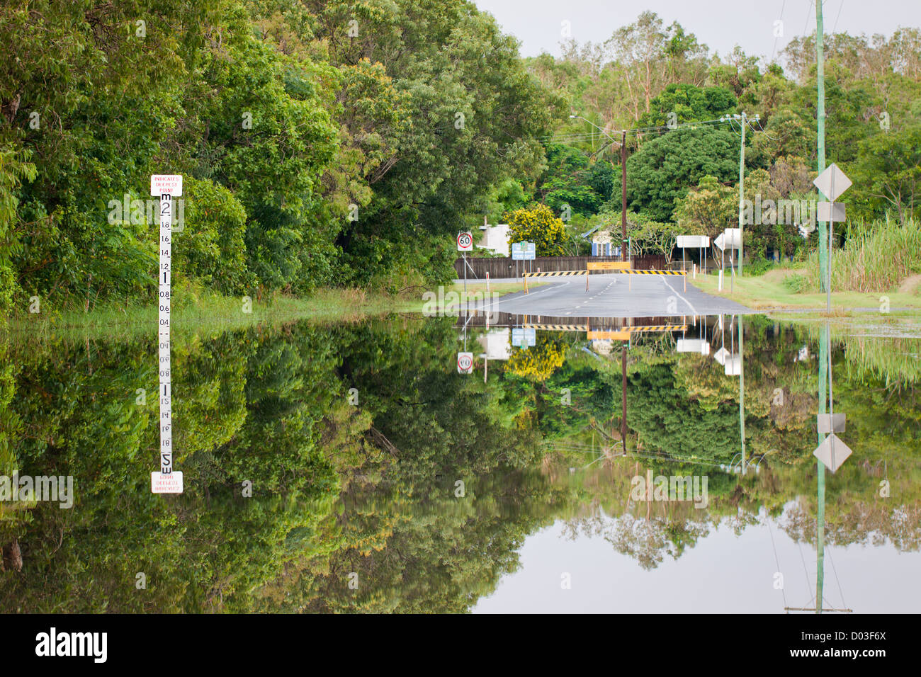 A flooded road with depth indicators and beautiful reflections - Stock Image