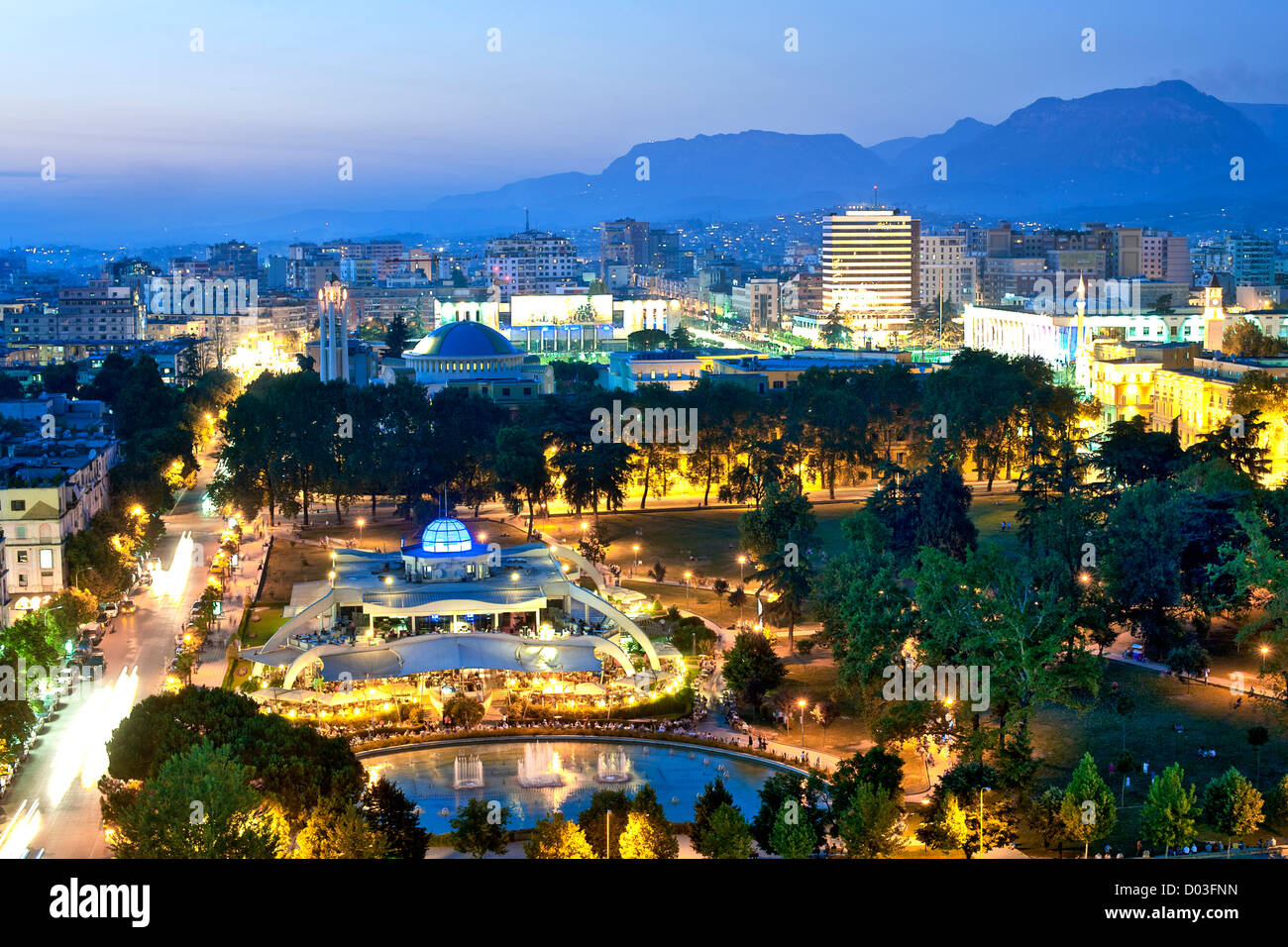 Dusk view of Tirana, the capital of Albania. In the foreground is Rinia Park. - Stock Image