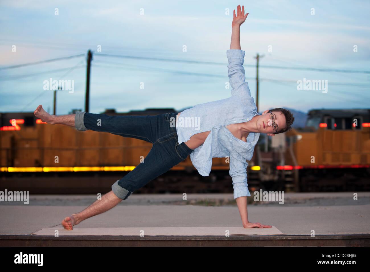 Caucasian man performing the Half Moon yoga position - Stock Image
