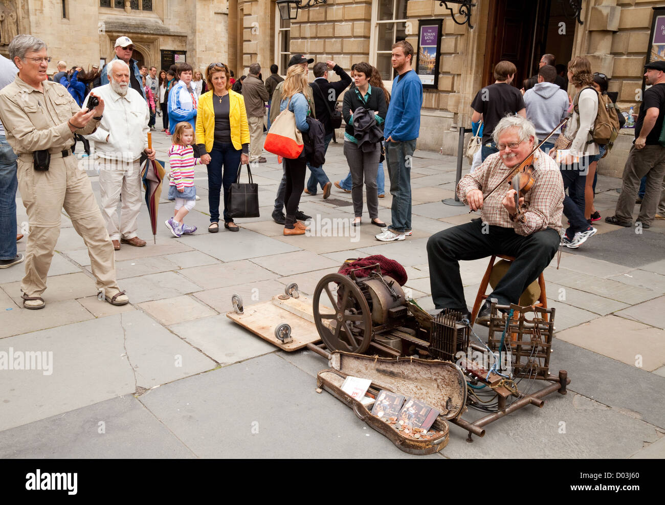 An old senior man busking in the street with his violin, Bath Somerset UK - Stock Image