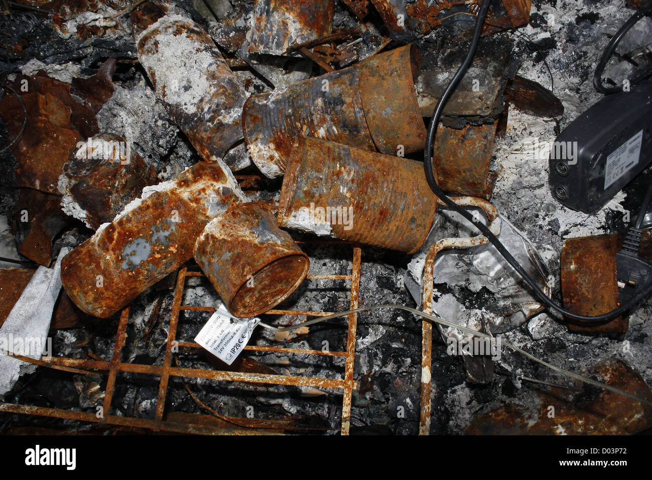 burnt tin cans in old shopping trolley - Stock Image