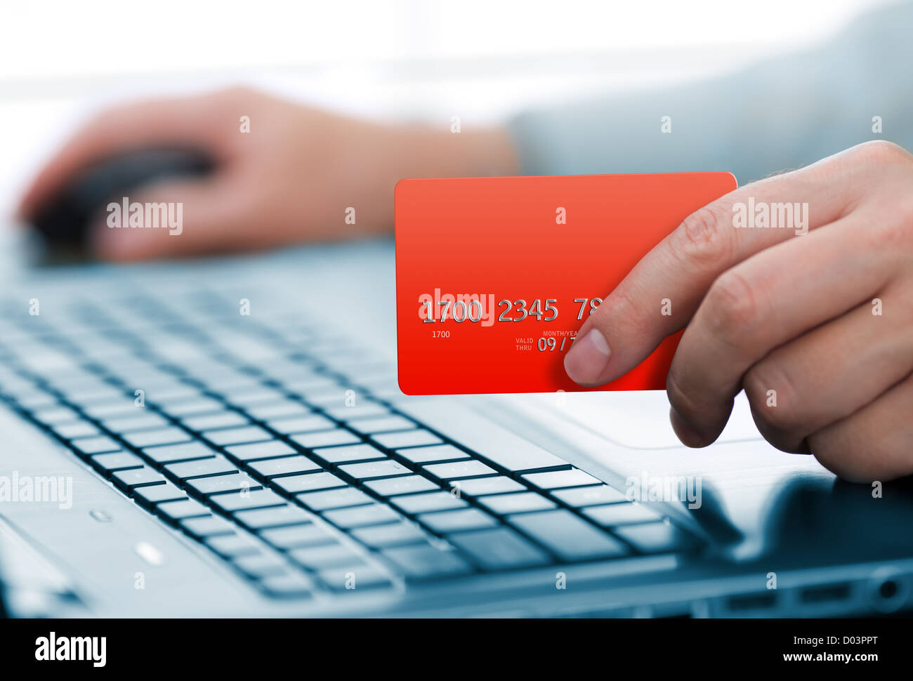 Man holding credit card in hand and entering security code using laptop keyboard - Stock Image