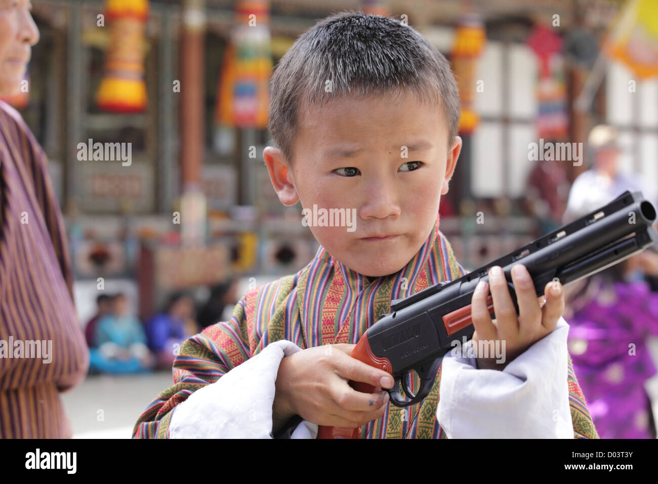Little monk standing with a toy gun performing art at a festival in Bhutan - Stock Image