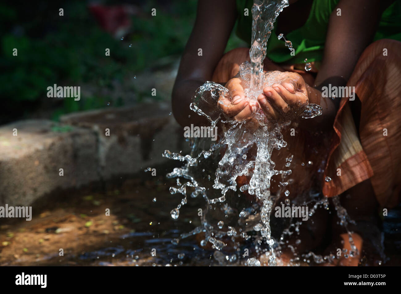 Water from a hand pump in a rural indian village pouring into an Indian girls hands. Andhra Pradesh, India. Stock Photo