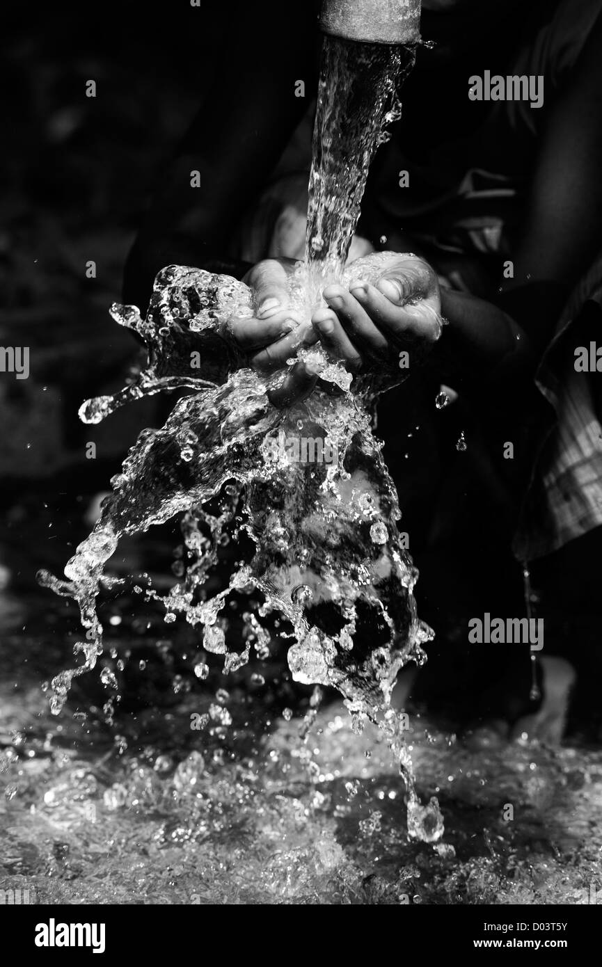 Water from a hand pump in a rural indian village pouring into an Indian girls hands. Andhra Pradesh, India. Monochrome Stock Photo
