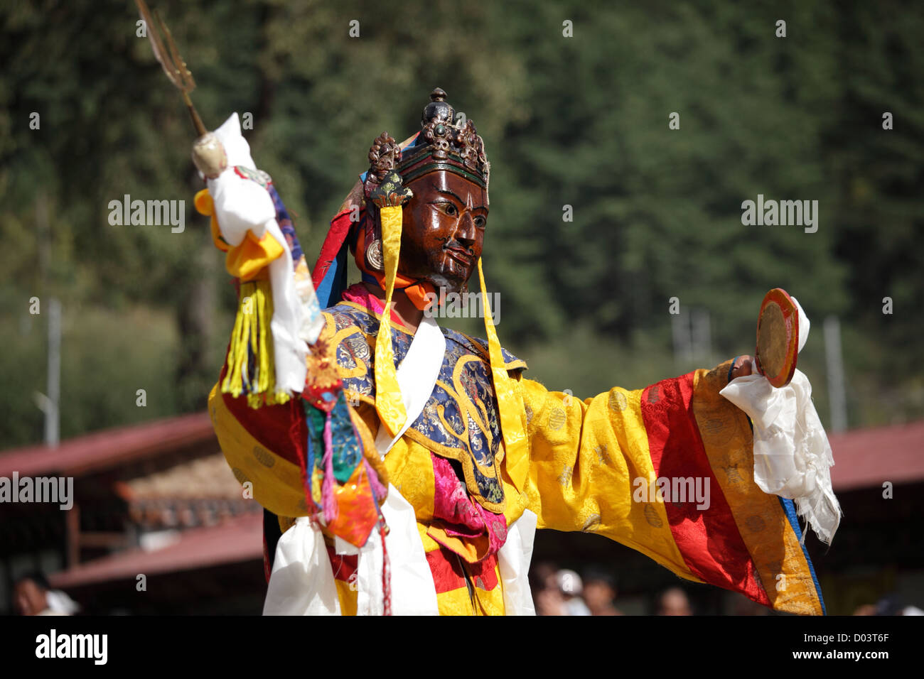 Buddhist monks dancing in traditional costumes with terrifying masks during religious festival in Bhutan. - Stock Image