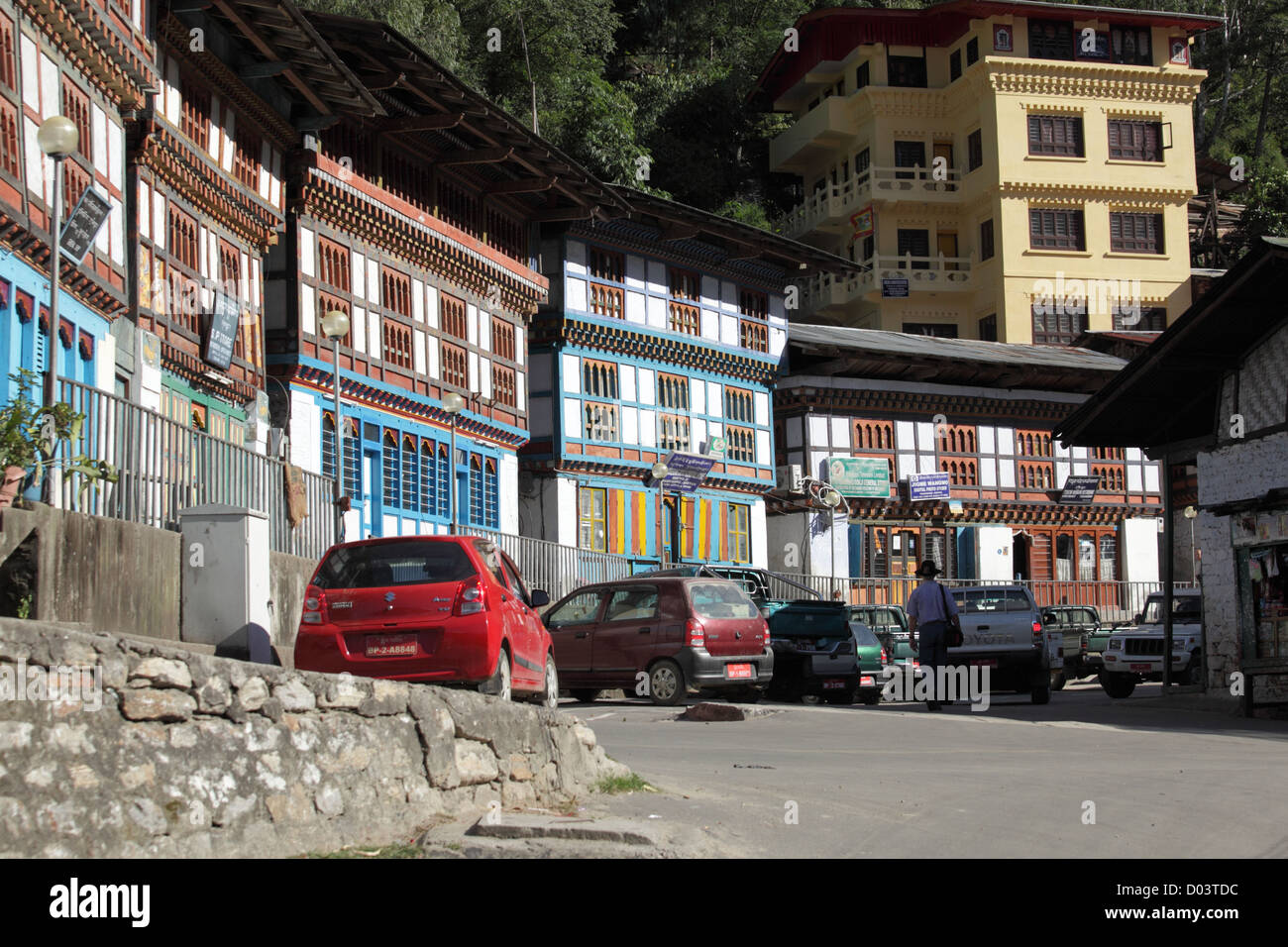A street in Bhutan where cars are parked and the shops and local hotels built in the traditional Bhutanese architectural - Stock Image