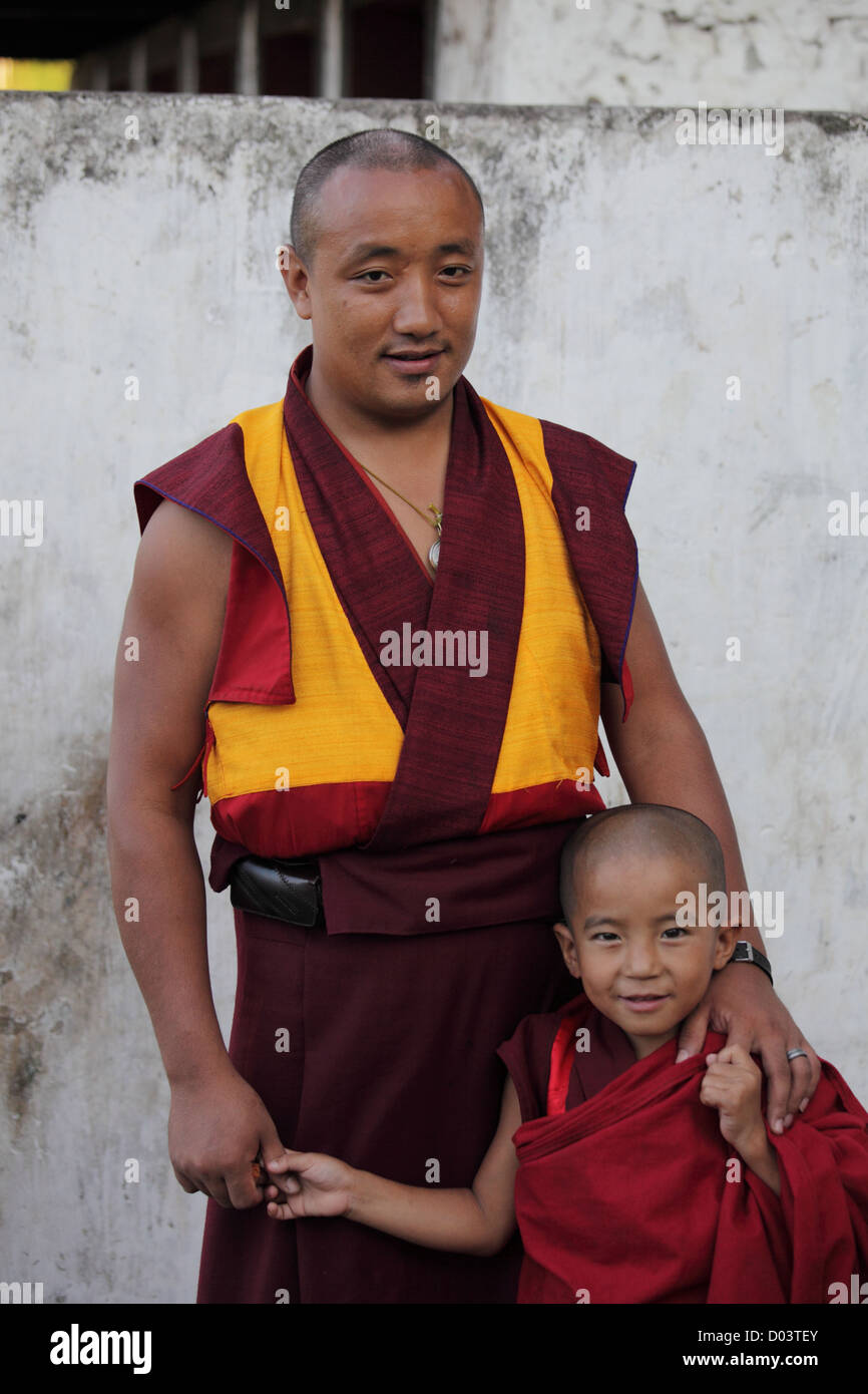 A father and toddler son stand together, each dressed in traditional Bhutanese dress. - Stock Image
