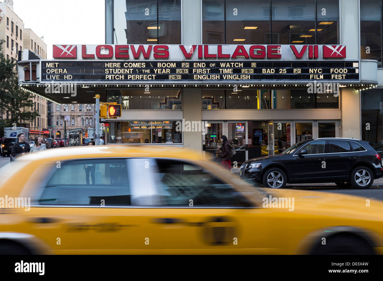 A yellow taxi passing in front the AMC Loews Village 7 theater in New York - Stock Image