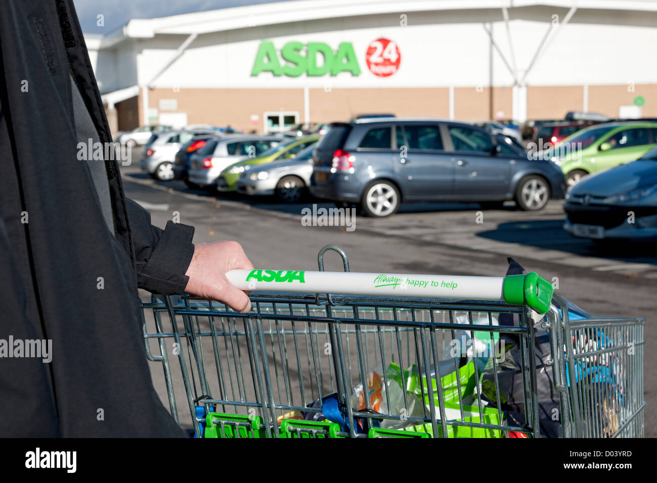 Man pushing ASDA shopping trolley in car park England UK United Kingdom GB Great Britain - Stock Image