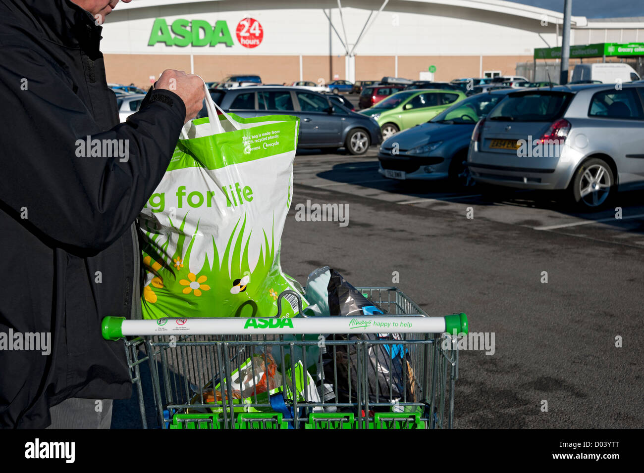 Man with ASDA shopping bags in trolley England UK United Kingdom GB Great Britain - Stock Image