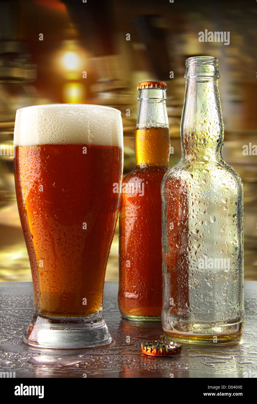 Glass of beer with bottles on counter - Stock Image