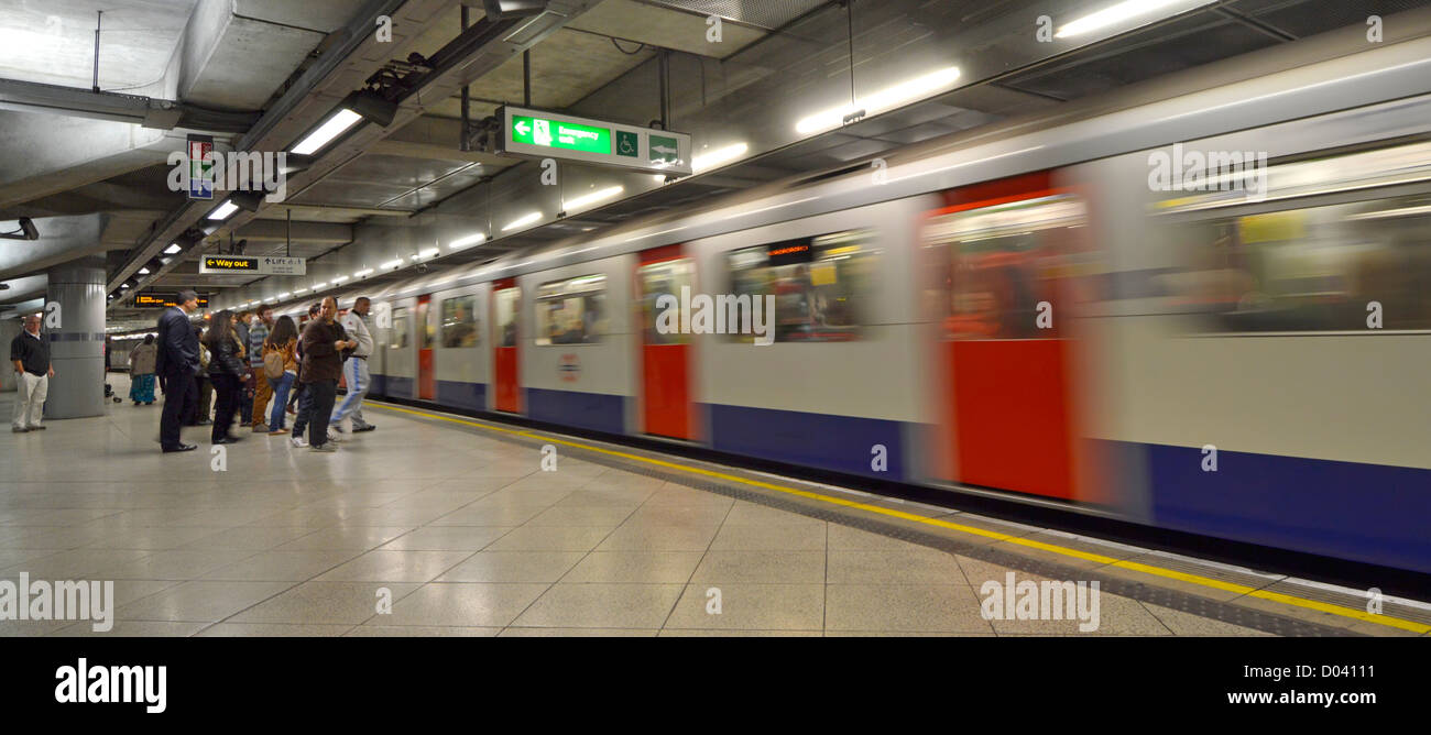 Westminster London underground tube station platform and motion blur train arriving London England UK - Stock Image