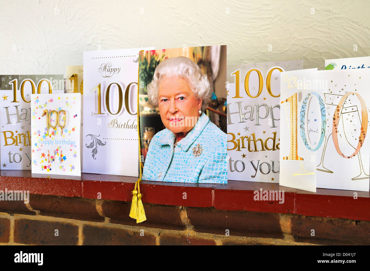 100th birthday cards alongside a personalised card from her majesty queen elizabeth ii on a mantelpiece
