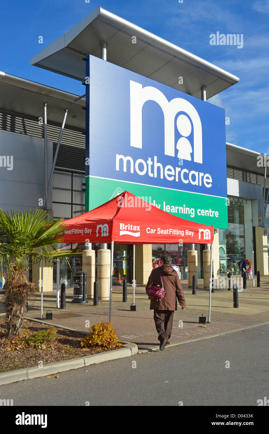 Woman walking towards Mothercare & Early Learning Centre entrance in large retail park with Britax Car Seat - Stock Image