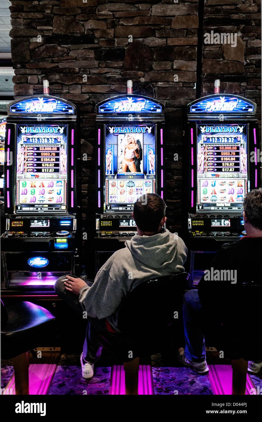 Men sit at slot machines in Foxwoods Resort Casino, Ledyard, Connecticut, USA - Stock Image