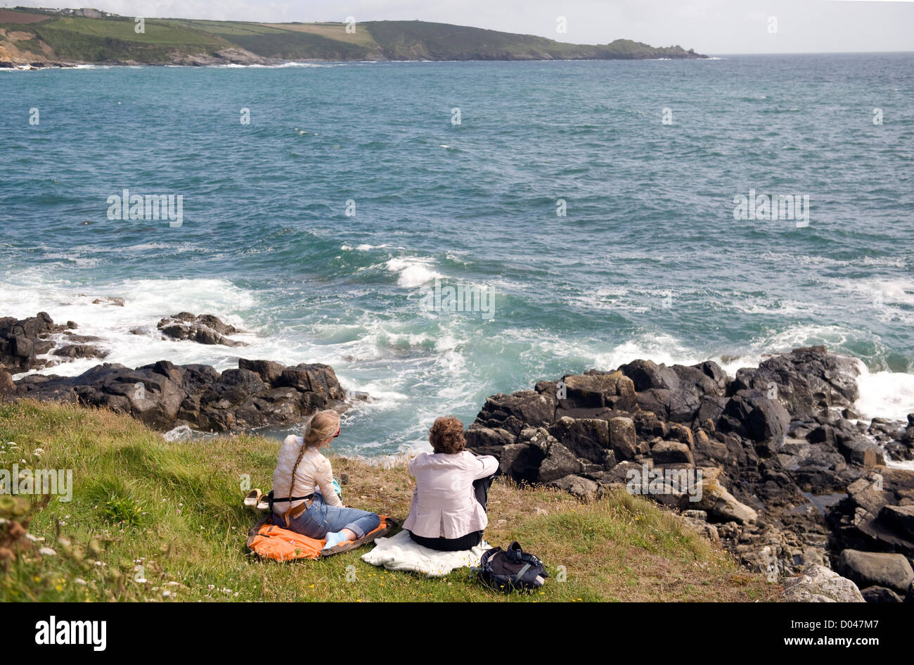 two  female holiday makers enjoying a rest on the south west coast path, england uk - Stock Image