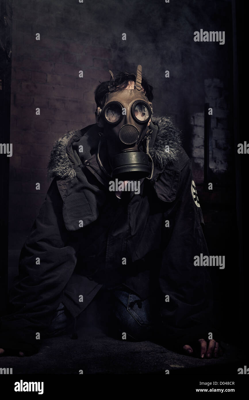 Man crouching in the darkness wearing a gas mask while shrouded in smoke - Stock Image