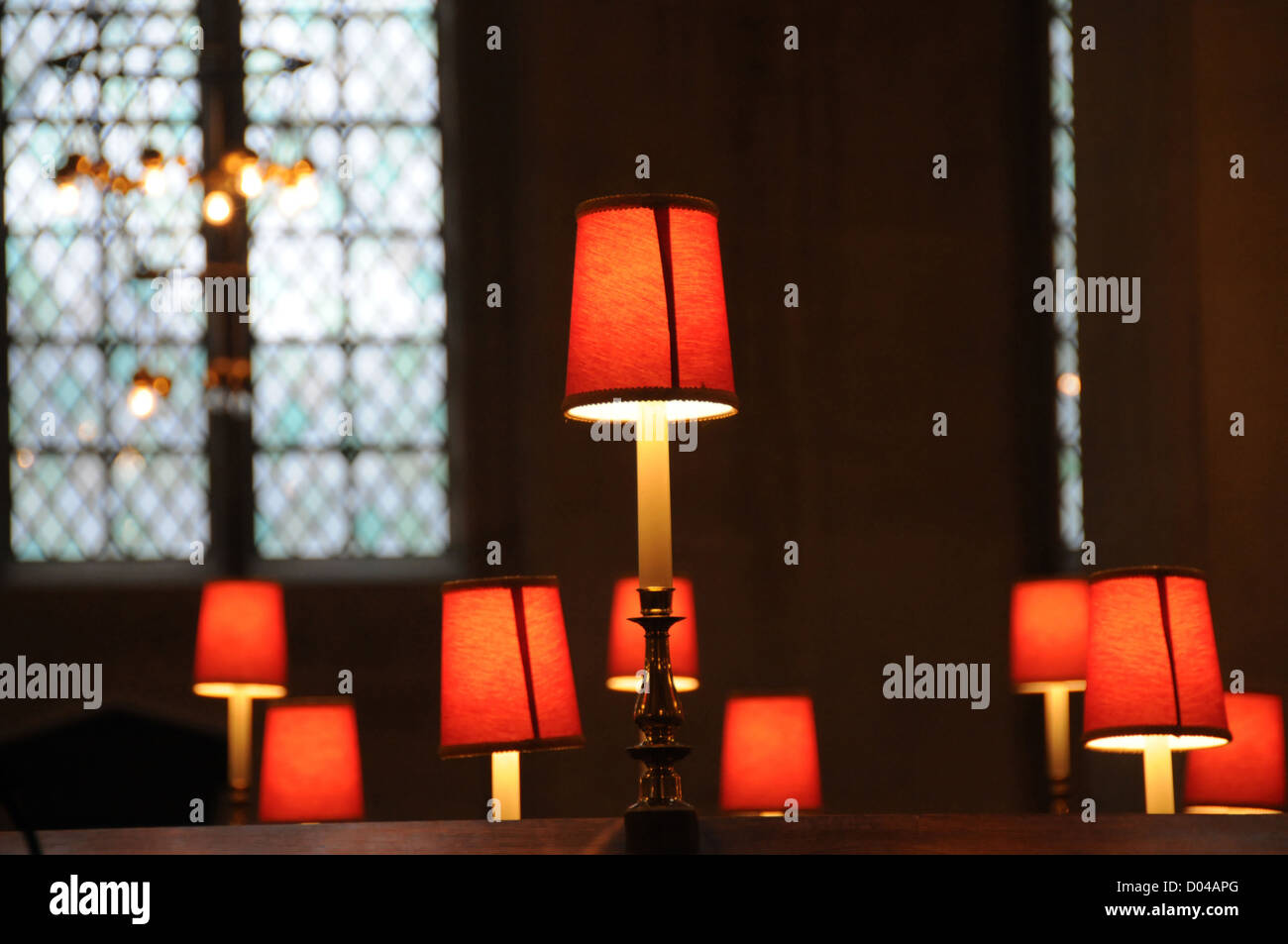 Small orange reading lamps on church pews with leaded window in rear. - Stock Image