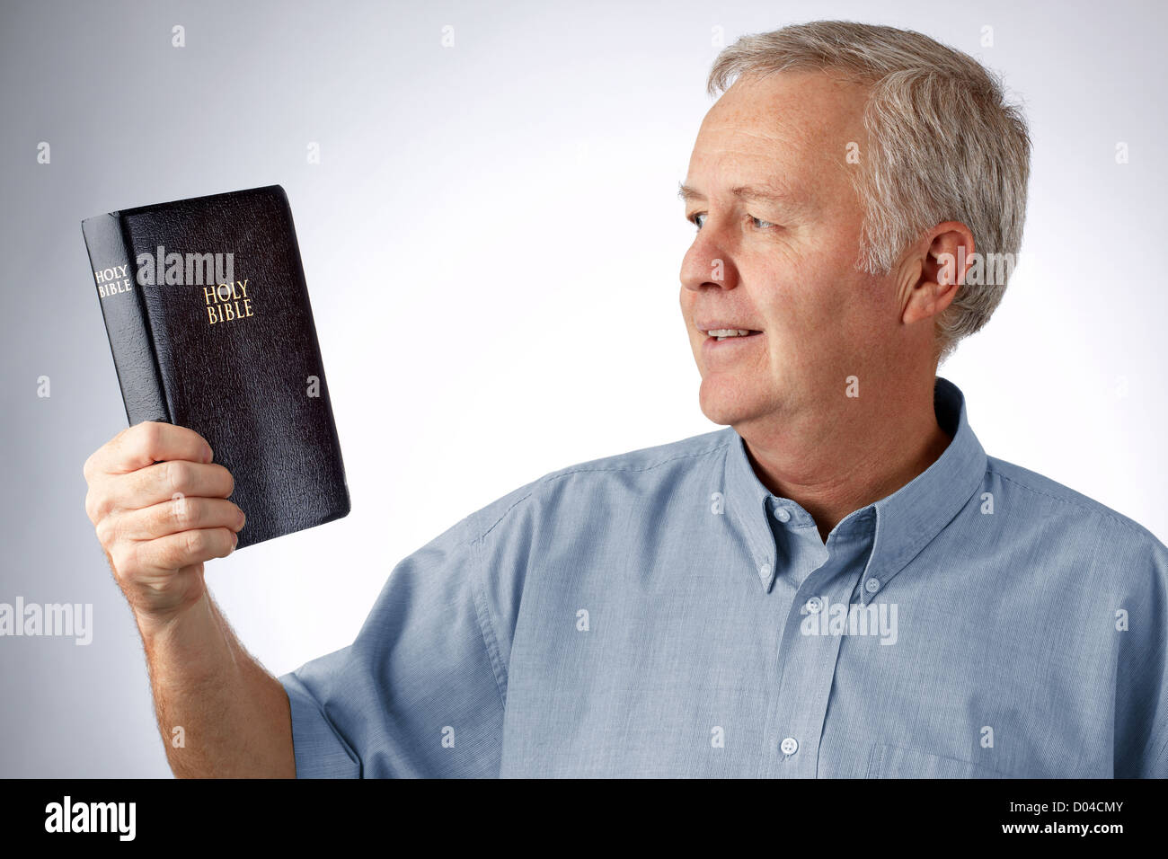 Man looking to the Bible in his hand (Open my eyes that I may see wonderful things in your law Psalm 119.18) - Stock Image