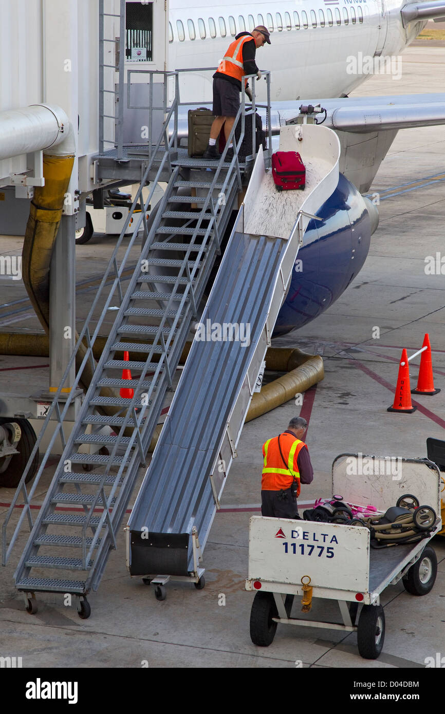 Two aircraft crew load baggage onto airplane on tarmac - Stock Image