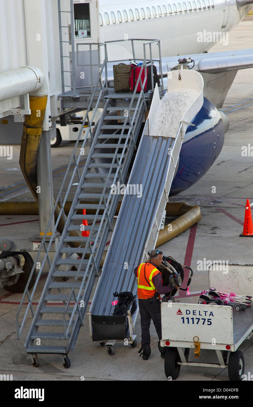 Baggage crew member loads luggage onto aircraft on tarmac - Stock Image
