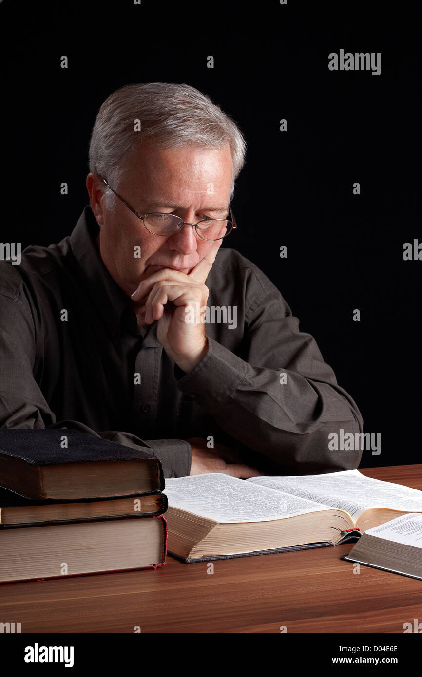 Senior pastor meditating and searching guidance - Stock Image