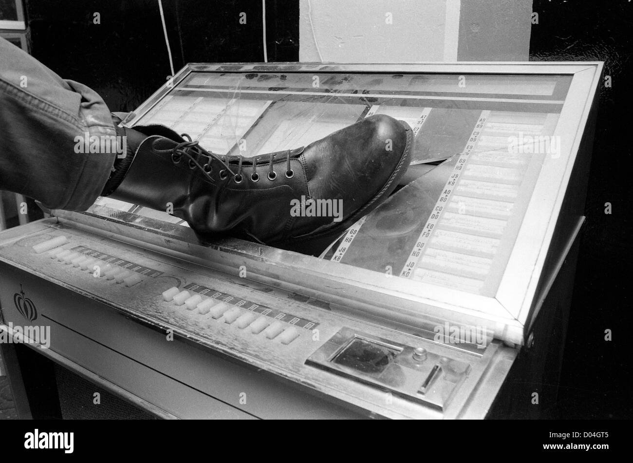 Vandalising a juke box with a boot during the punk period 1979 PICTURE BY DAVID BAGNALL - Stock Image