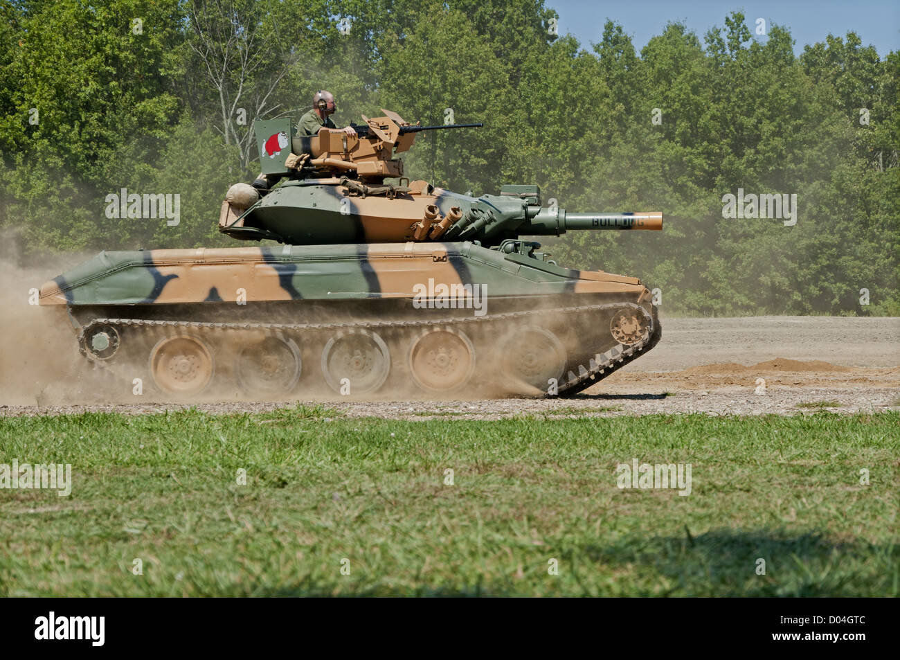 A camouflaged US Army M551 Sheridan light tank moving at speed over open ground. Sheridans first saw combat in Vietnam - Stock Image