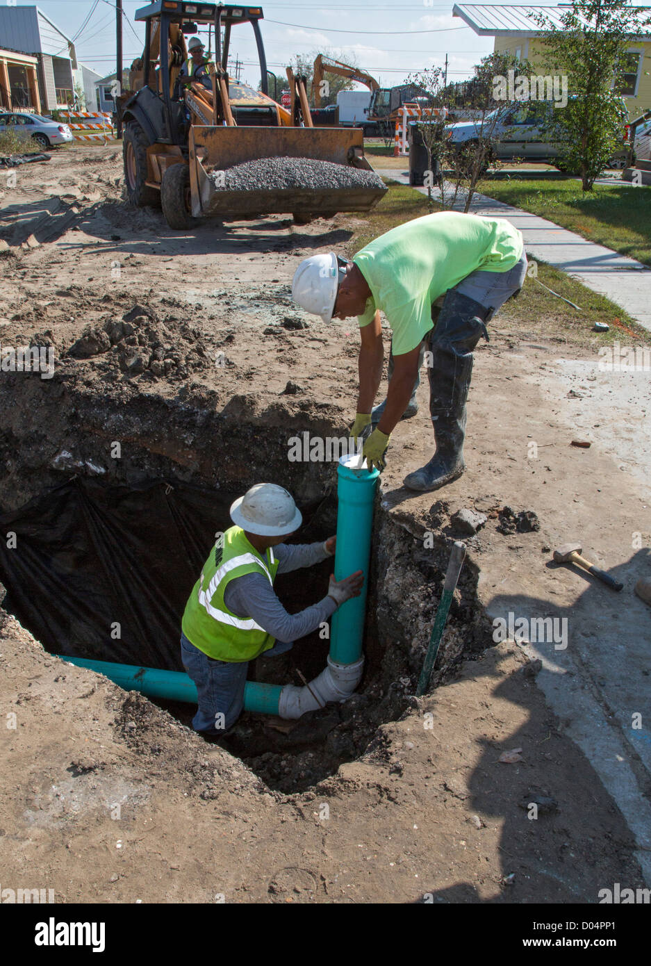 Seven years after Hurricane Katrina, workers hook up a sewer line to a new home in New Orleans' lower ninth - Stock Image