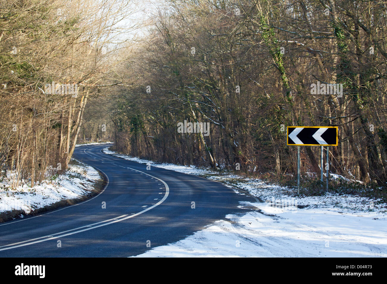 Countryside road and bends with left-pointing Road Bend Direction Sign - Stock Image