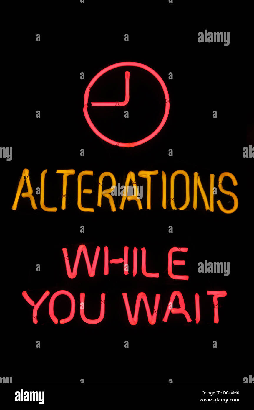 Alterations While You Wait Pink Neon Sign - Stock Image