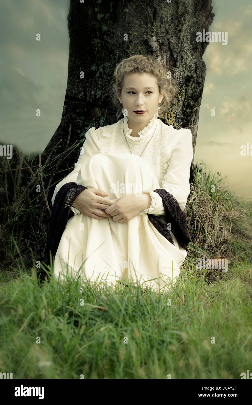 a girl in a victorian dress is sitting under a tree - Stock Image