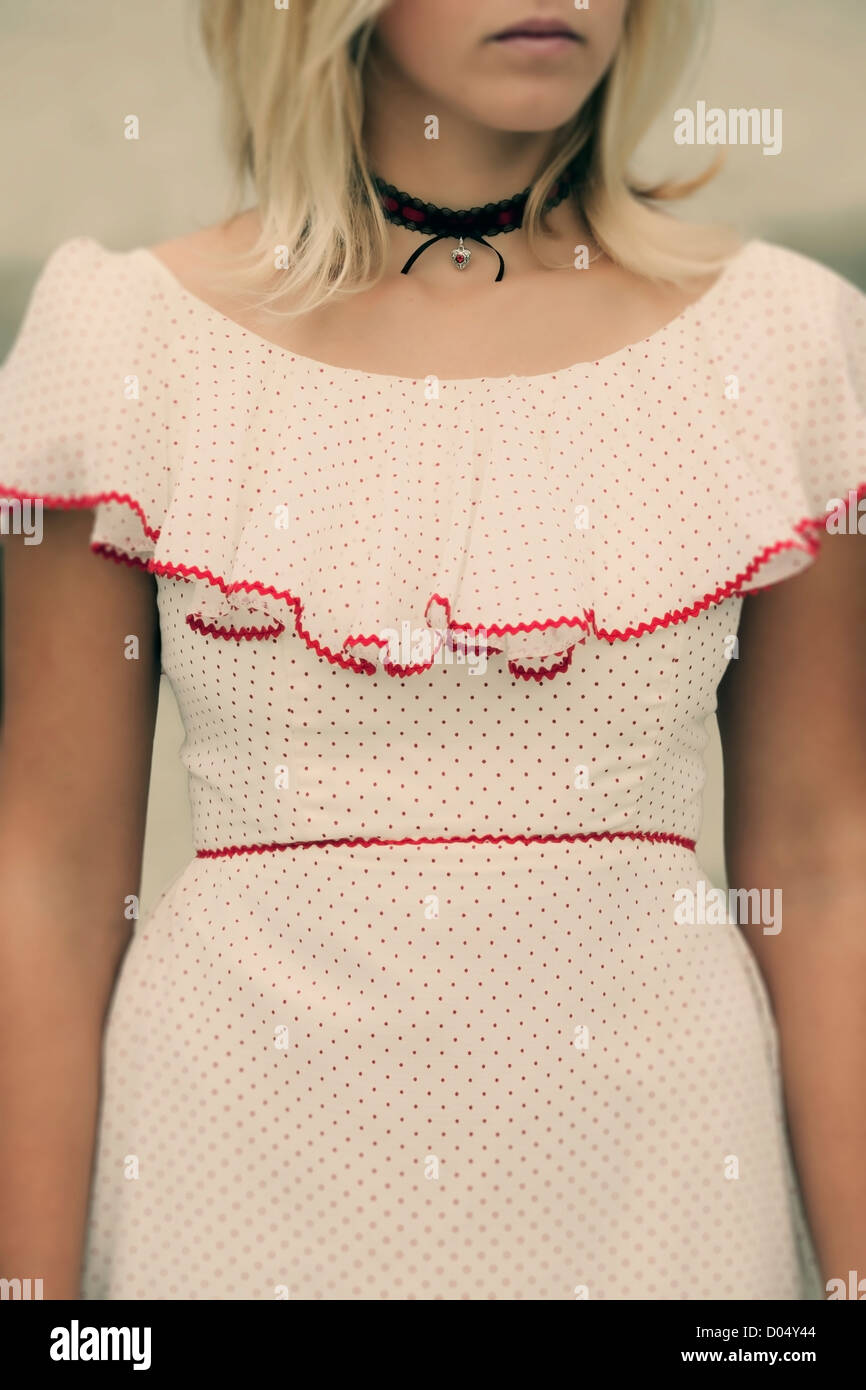 a woman in a white dress with red polka dots - Stock Image