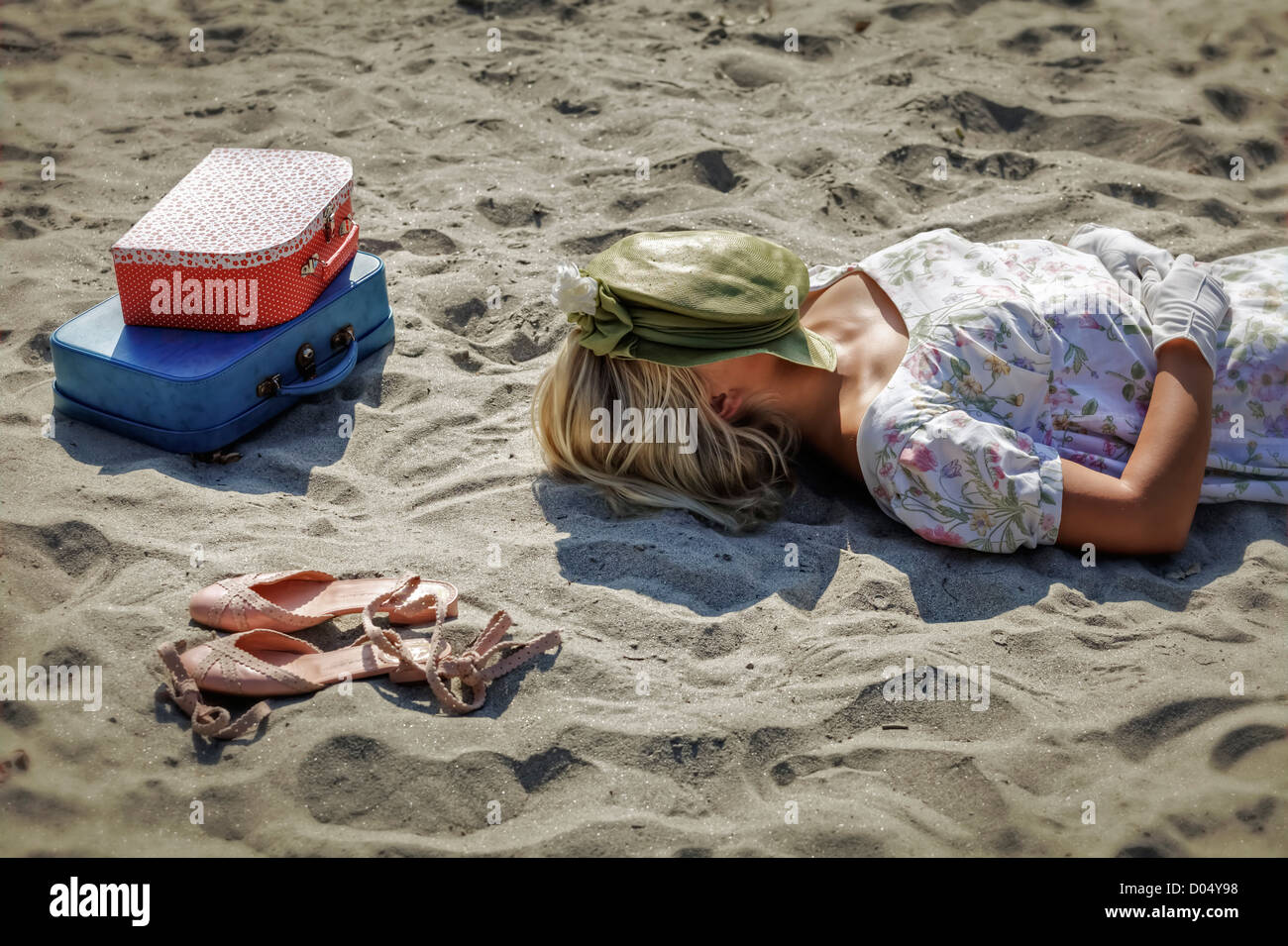 a woman in a floral dress is lying on a beach next to her shoes and two vintage suitcases - Stock Image