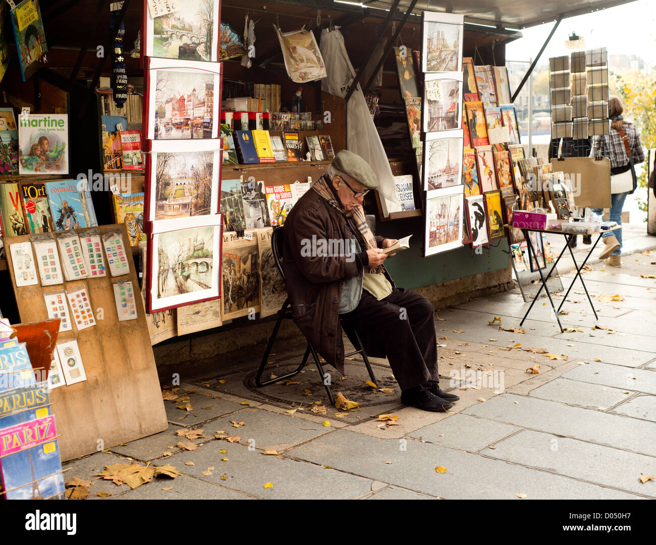 A book seller on the left bank of the Seine, sitting reading in front of his stand - Stock Image