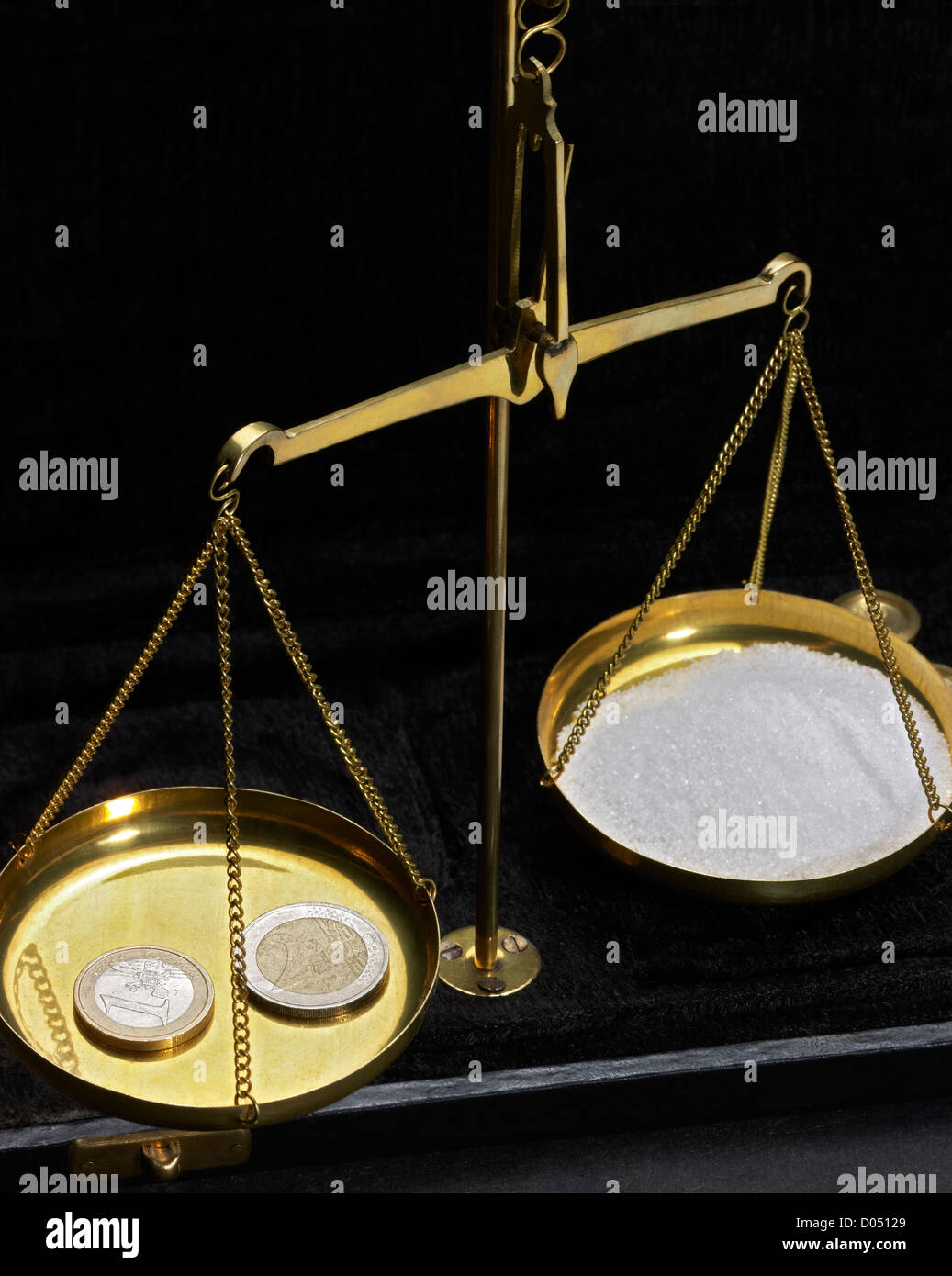 historic scales with euro coins and sugar in dark back Stock