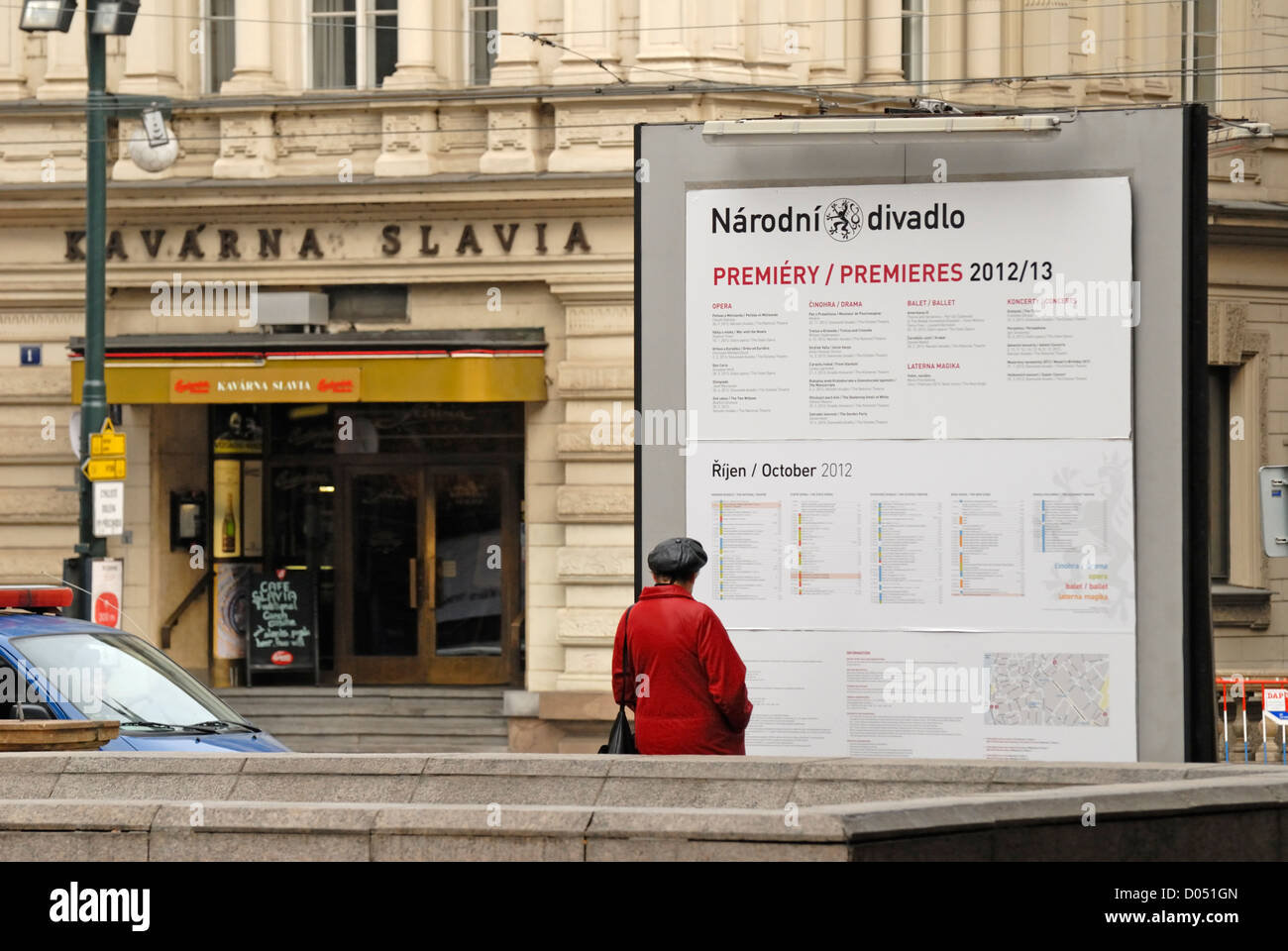 Prague, Czech Republic. Narodni (street) Woman looking at National Theatre programme - Cafe Slavia behind - Stock Image