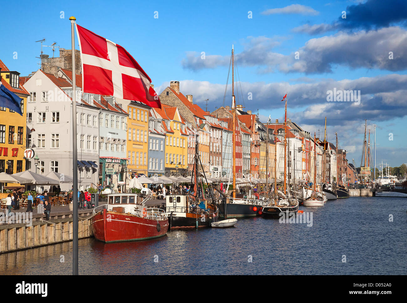 COPENHAGEN, DENMARK - AUGUST 25: Unidentified people enjoying sunny weather in open cafees of the famous Nyhavn - Stock Image