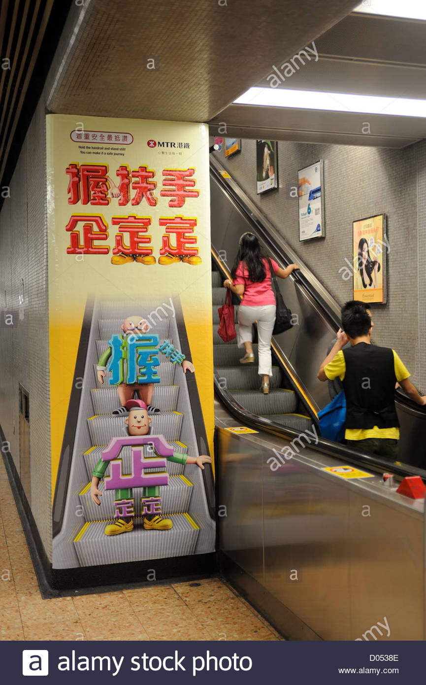 Hong Kong Posters on the MTR metro telling people to hold on to the handrail when using the escalator. - Stock Image