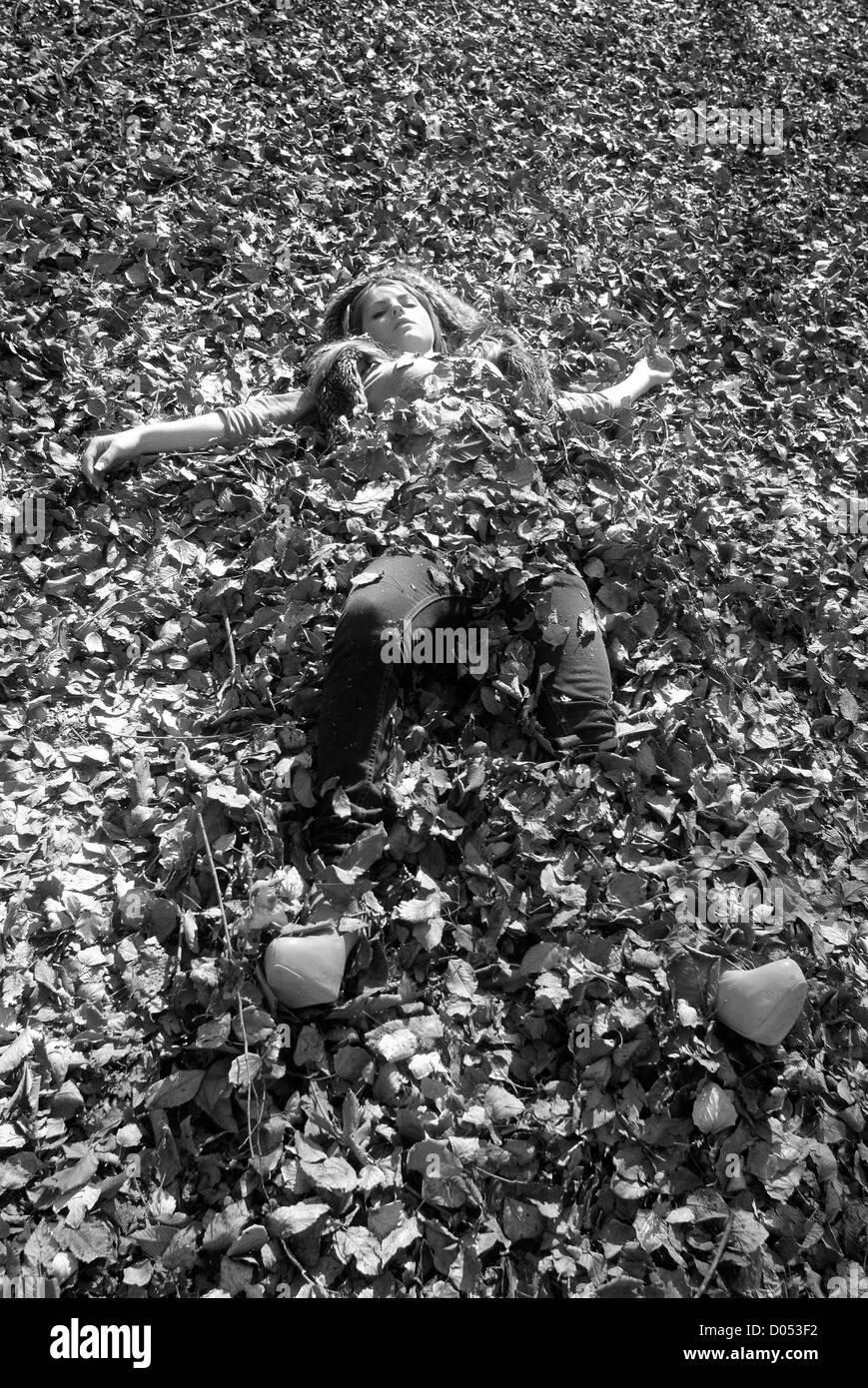 Woman buried in oak leafs Stock Photo