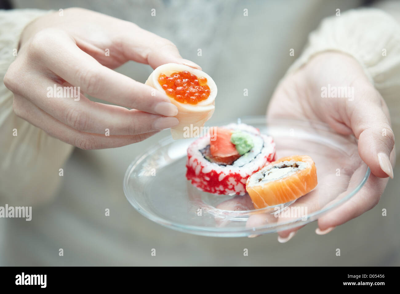 Human hands holding place with sushi - Stock Image