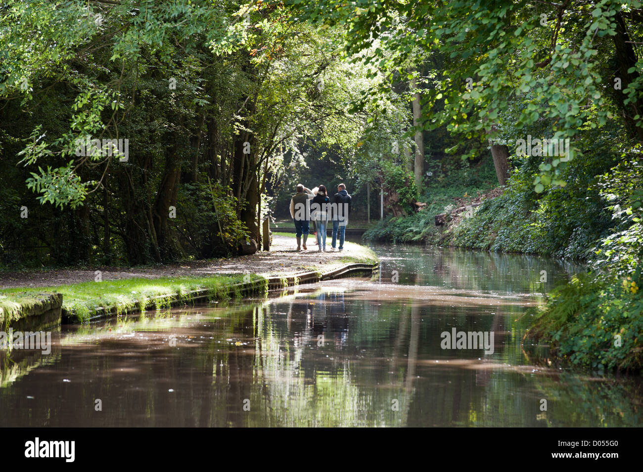 people walking next to a canal with sunlight through the trees - Stock Image