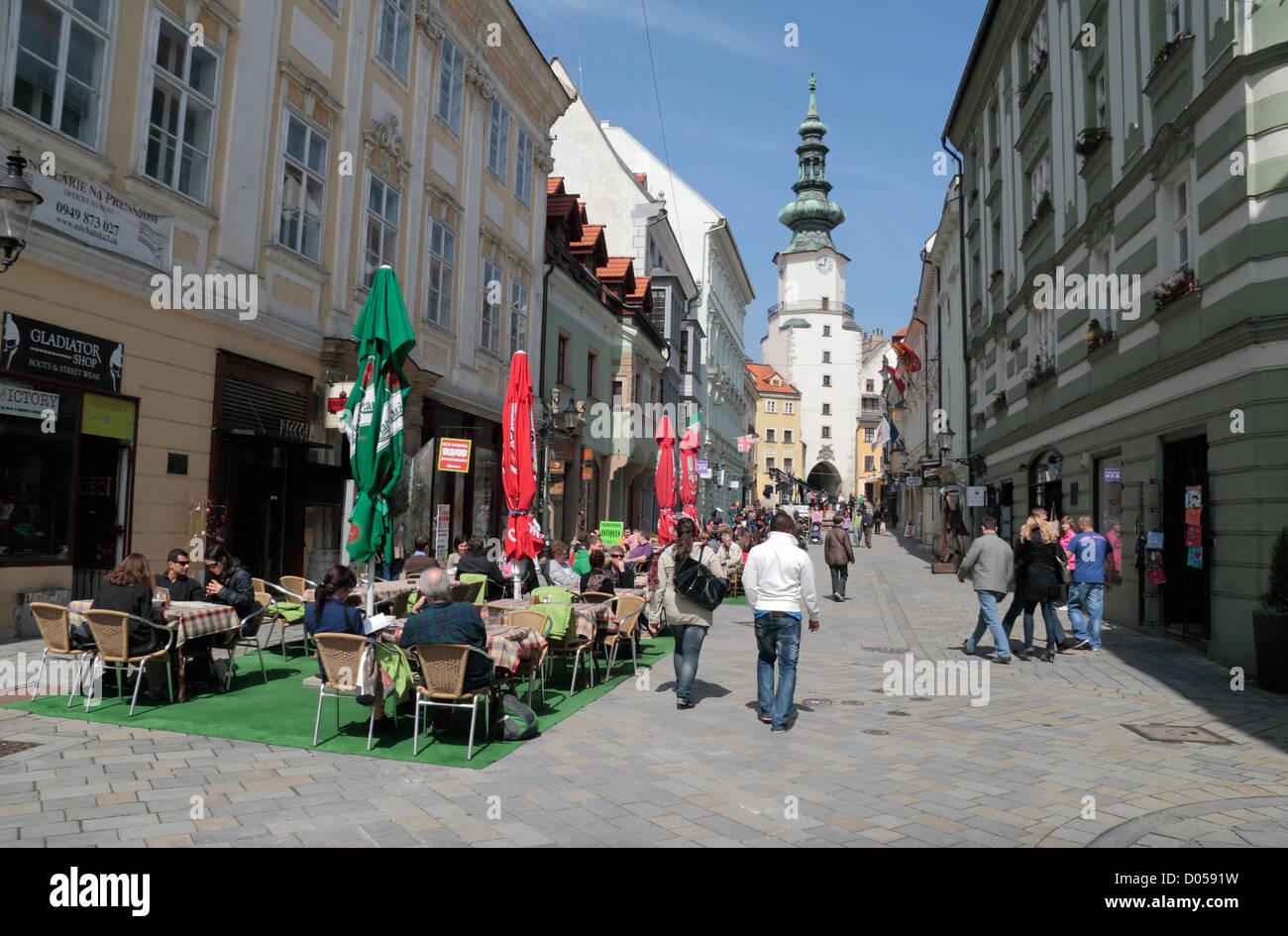 Cafe culture on Michalská Street looking up towards Michael's Gate (Michaelertor) in Bratislava, Slovakia. - Stock Image