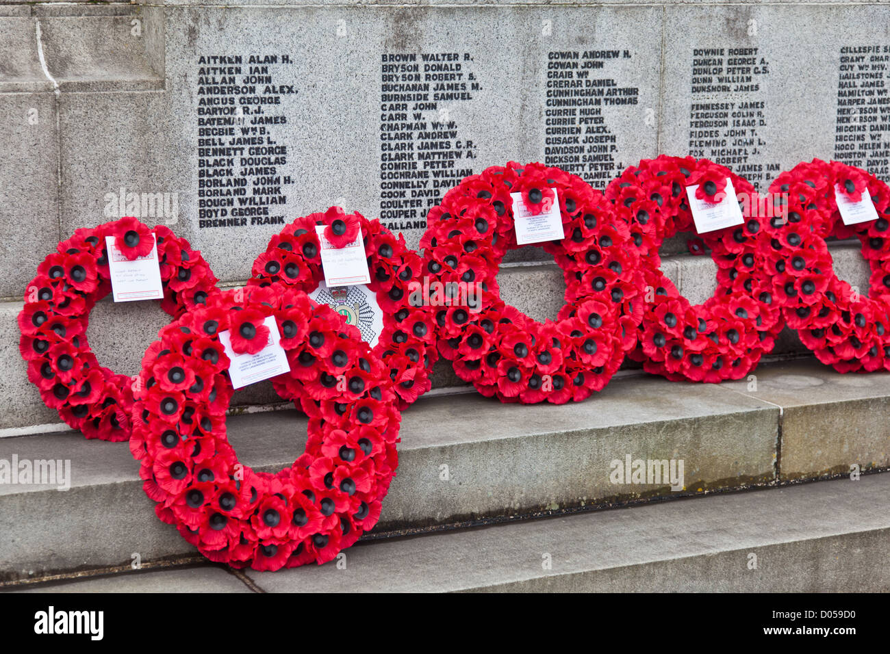 Poppy wreaths laid at the cenotaph in Centenary Park, Airdrie, North Ayrshire, Scotland, UK. Remembrance Sunday, - Stock Image