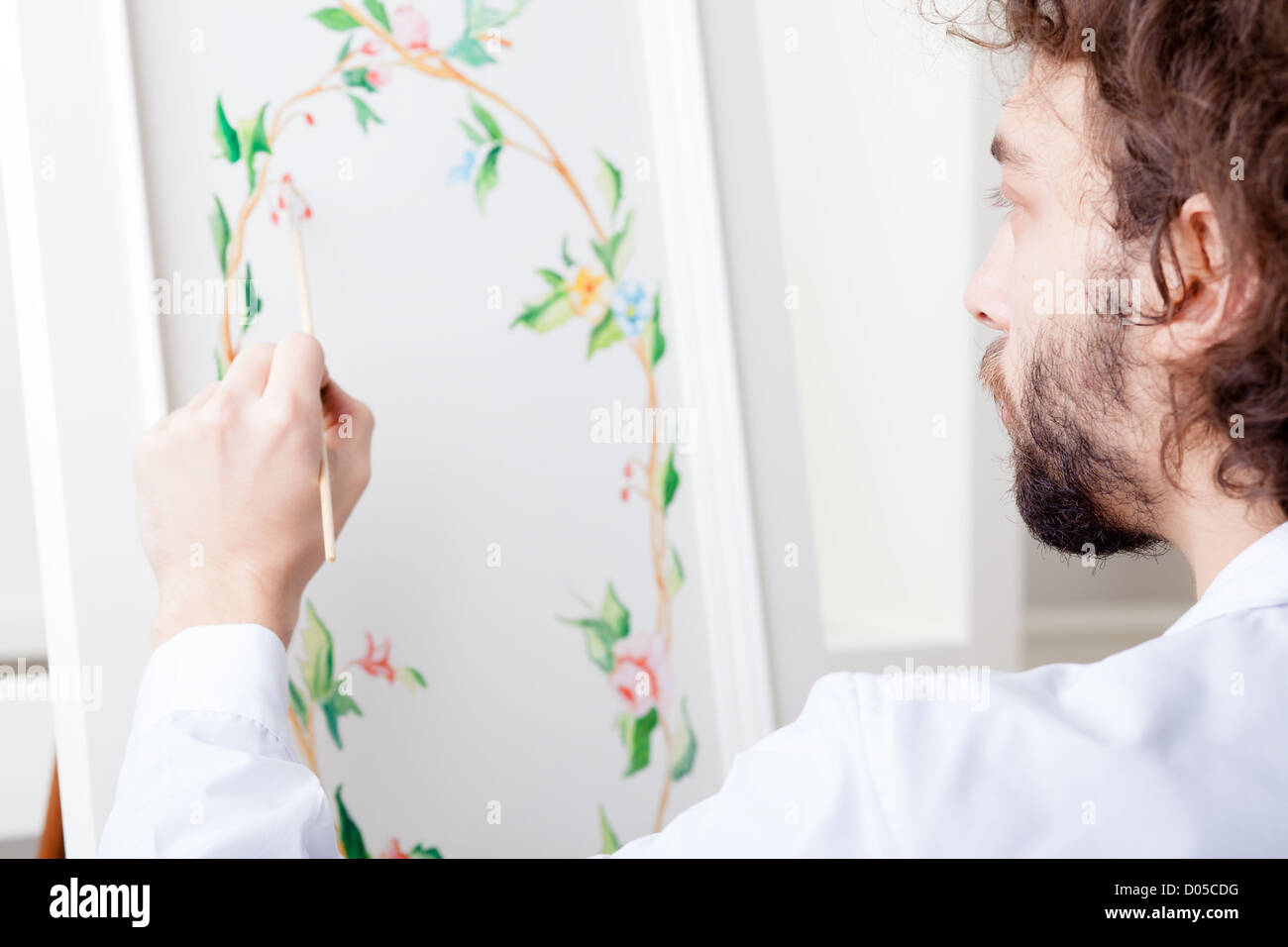 Decorator Painting Flowers on Furniture in His Workshop - Stock Image