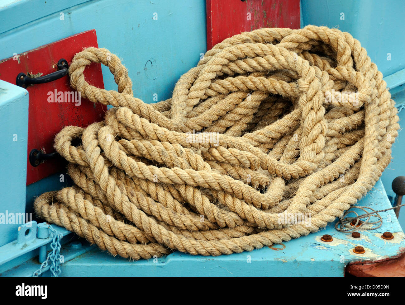 A coil of natural fibre rope in a fishing boat. Scrabster, Caithness, Scotland, UK. - Stock Image