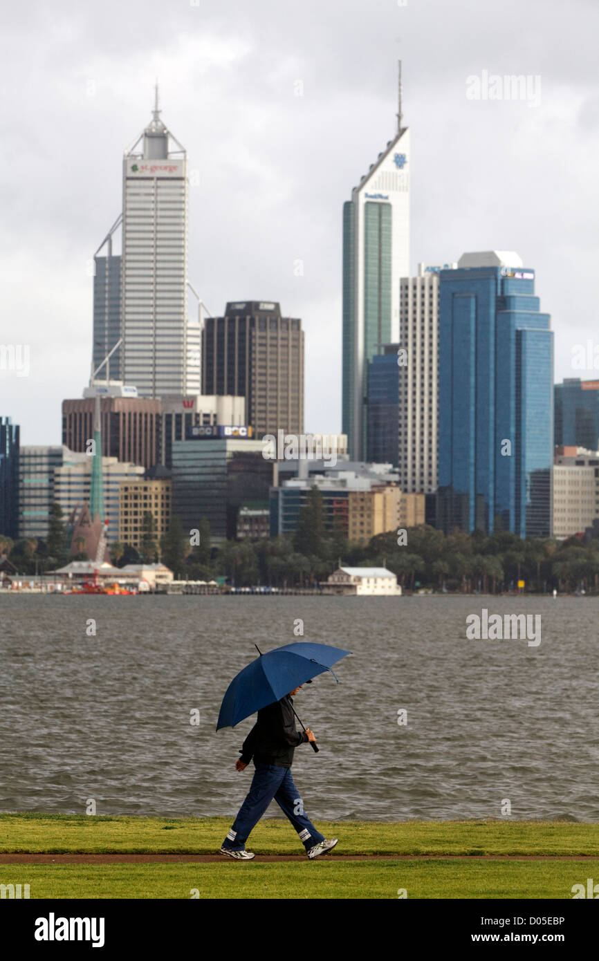 A man walking in the rain holding an umbrella with a city skyline in the background - Stock Image
